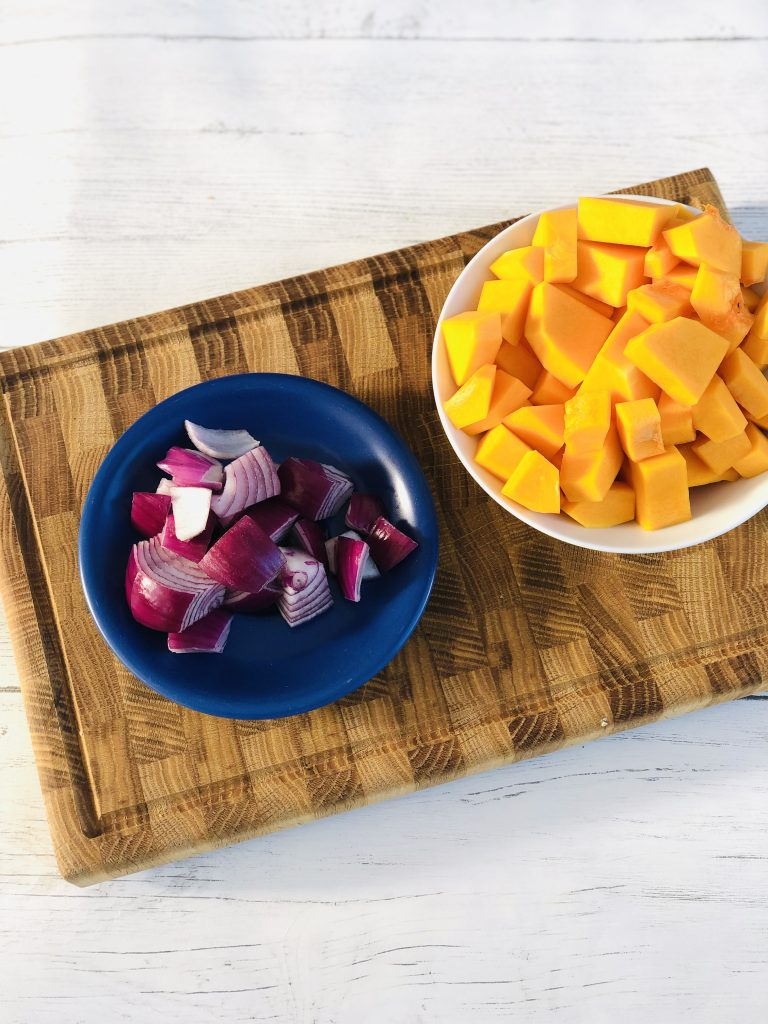 wooden block chopping board with blue saucer filled with chunkily chopped red onions next to a white bowl filled with peeled butternut squash chopped into bitesized pieces