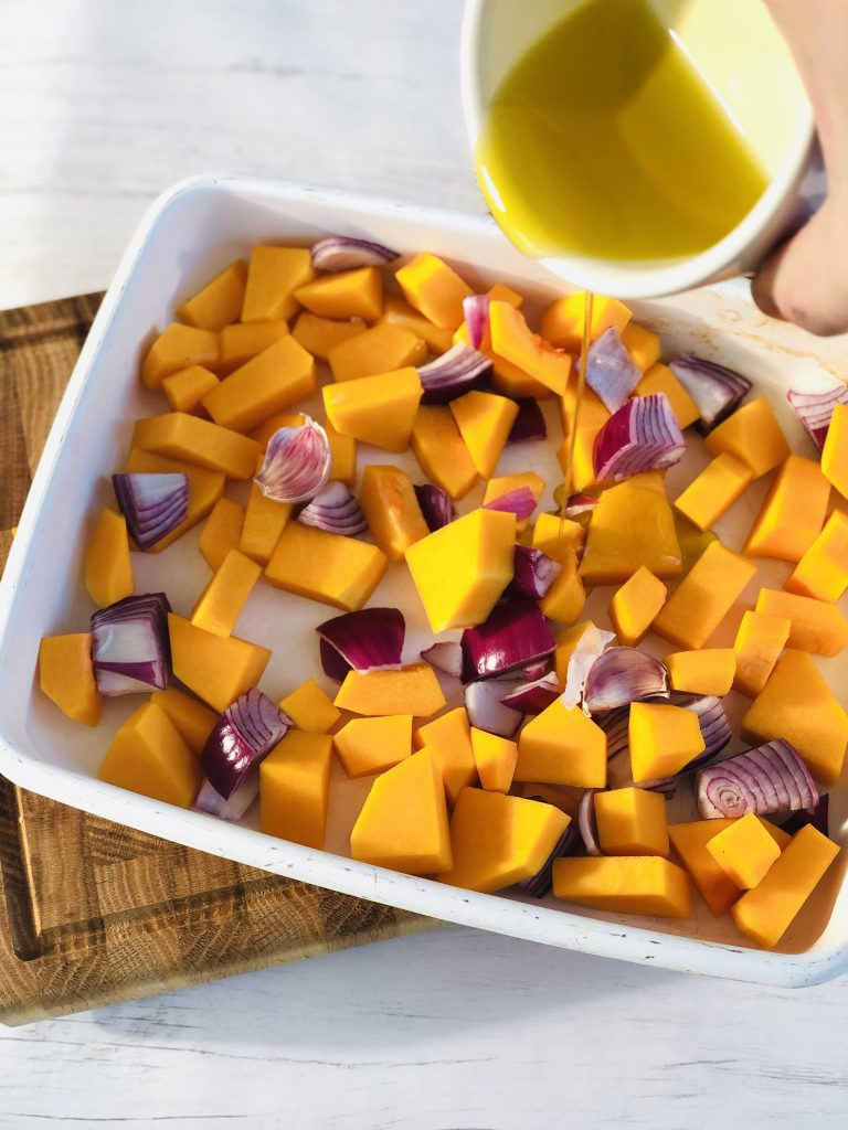 wooden block chopping board with white enamel roasting tin resting on top of it. Enamel roasting tin is filled with butternut squash and red onions chopped into bitesized pieces - small white bowl with olive oil in it is being poured into the roasting tin.