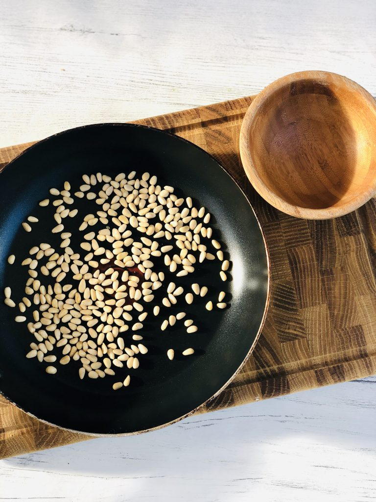 wooden block chopping board on a white table - frying pan on top of chopping board filled with pine nuts - small empty wooden bowl to the side of the pan