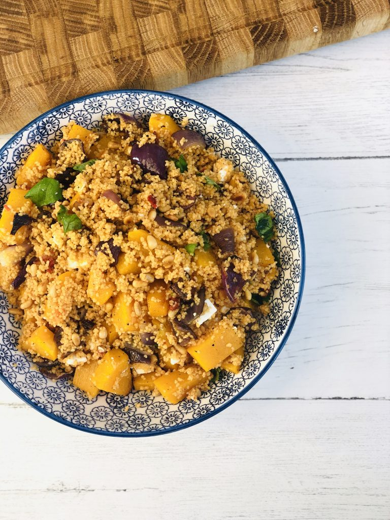 blue and white flower patterned bowl filled with roast squash and feta couscous with toasted pine nuts and fresh torn basil leaves