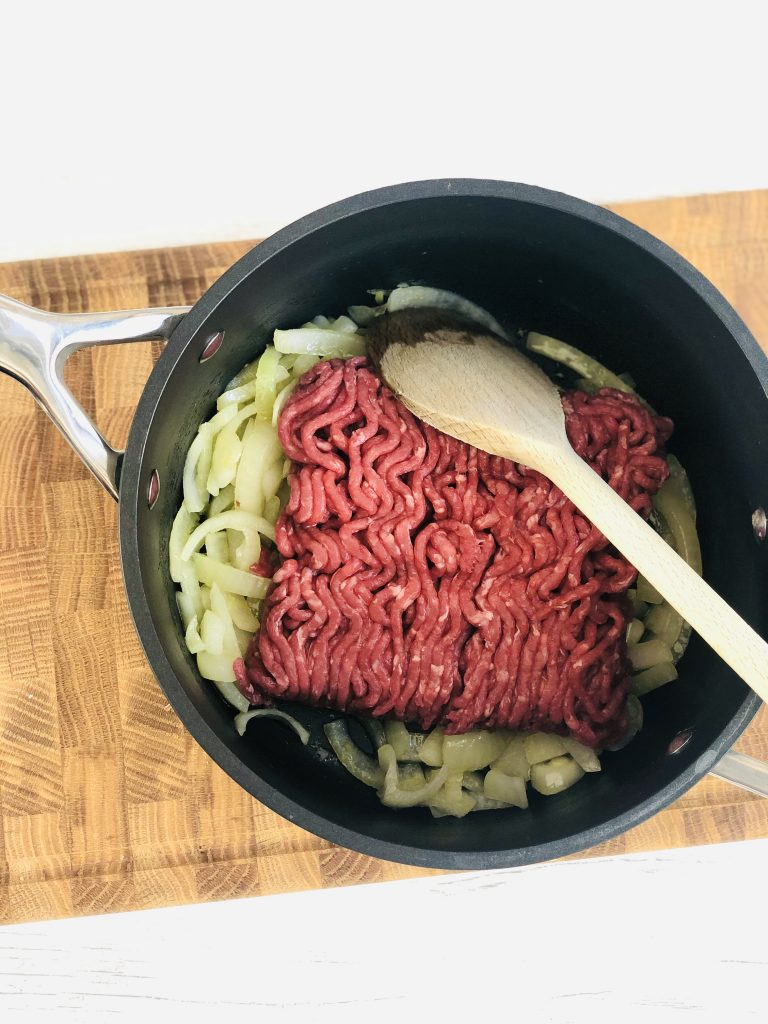 wooden block chopping board with sautéed chopped onions and a pack of beef mince tipped into the pan waiting to be broken up and browned off