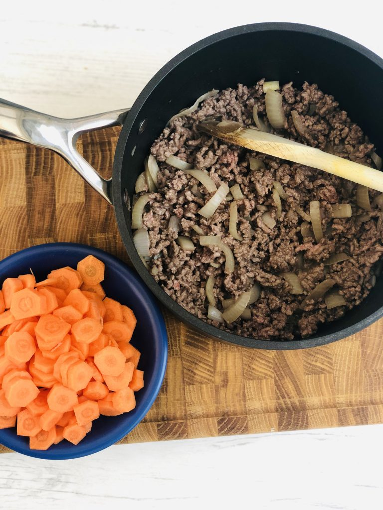 Le Creuset black saucepan filled with sauted onions and beef mince, blue saucer to the side filled with peeled, sliced carrots.