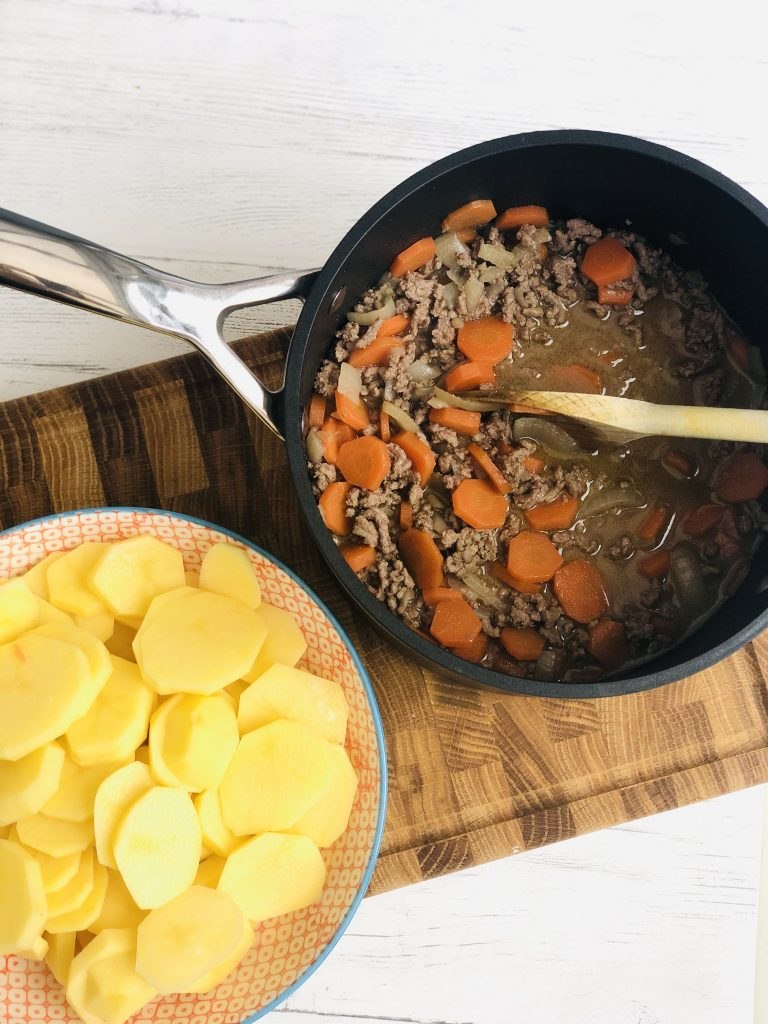 black Le Creuset saucepan filled with boiled beef mince, onion and carrot with a bowl of peeled sliced potatoes ready to tip into the stew