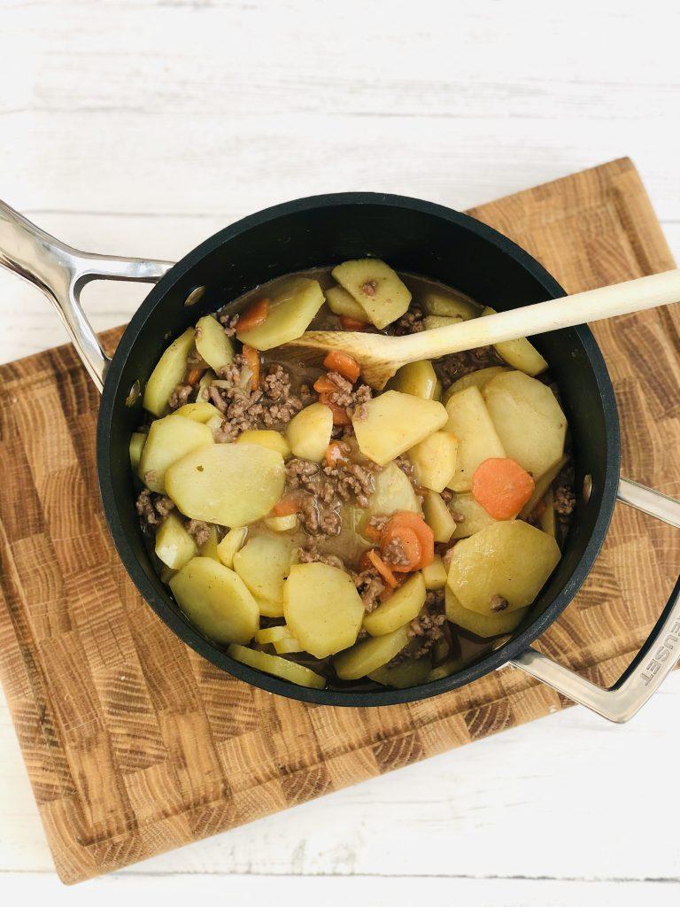 black Le Creuset saucepan filled with lancashire potato hash ready to cook