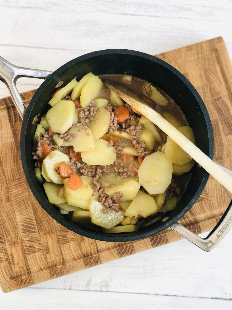 black le creuset saucepan filled with Lancashire potato hash
