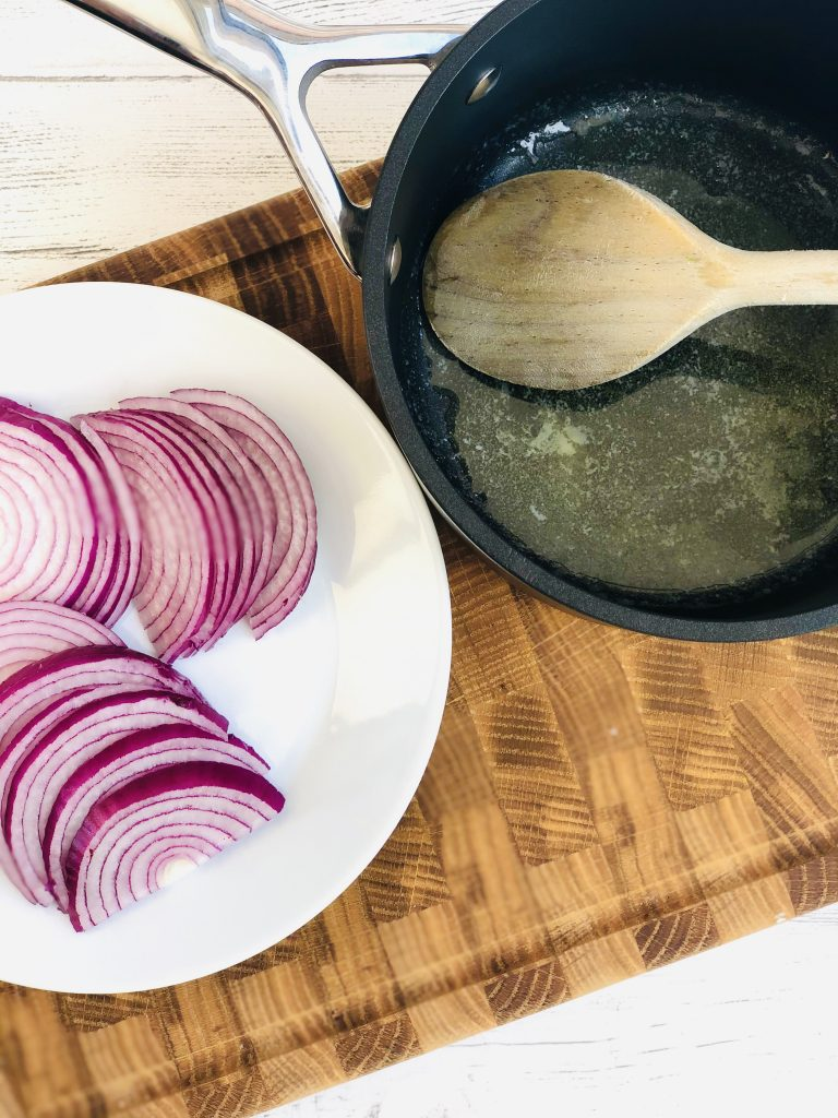 white plate with red onion chopped into half moons in a pile next to a black le creuset saucepan with melted butter in the bottom and a wooden spoon resting on the side of the pan