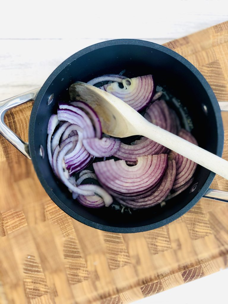 black le creuset saucepan with butter and sliced red onions tipped into it being stirred with a wooden spoon. Pan is on top of a wooden chopping board