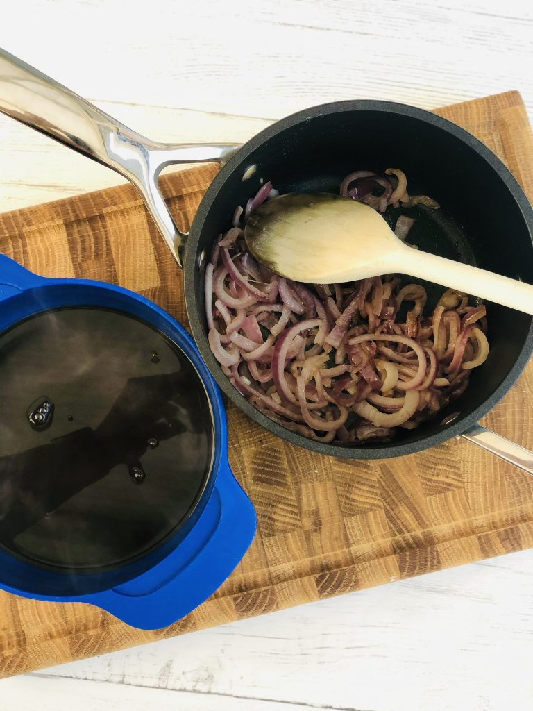 wooden chopping board with black le creuset saucepan on top filled with gently fried red onions in butter, next to the pan is a dark blue joseph joseph measuring just filled with Bisto best onion gravy