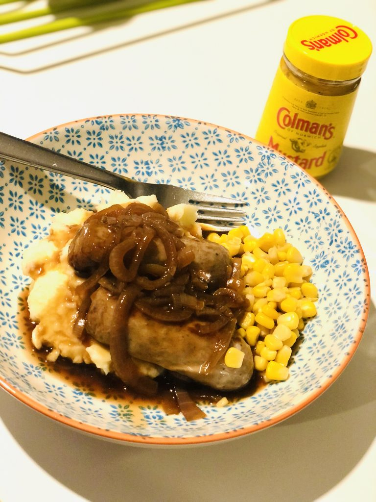 blue, white and orange flour patterned bowl filled with creamy mashed potatoes topped with two cumberland sausages and a dolloped with homemade onion gravy. Pile of sweetcorn nestles around the bottom of the mashed potatoes. Jar of Coleman's English mustard is by the bowl