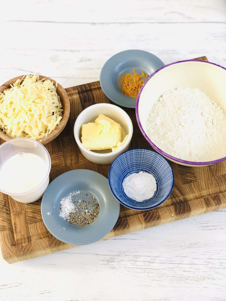 ingredients for gluten free cheese scone gathered on a wooden chopping board - white bowl with purple rim filled with gluten free flour, white bowl with block of butter in, blue and white bowl with baking powder in, small blue saucer with mustard powder on it, small blue saucer with salt and pepper on it, small wooden bowl filled with grated cheddar cheese, small plastic cup filled with milk