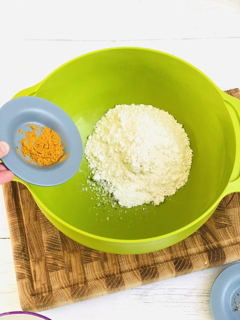 green joseph joseph mixing bowl with pile of Doves Farm gluten free flour, small saucer of mustard powder being tipped into the flour.