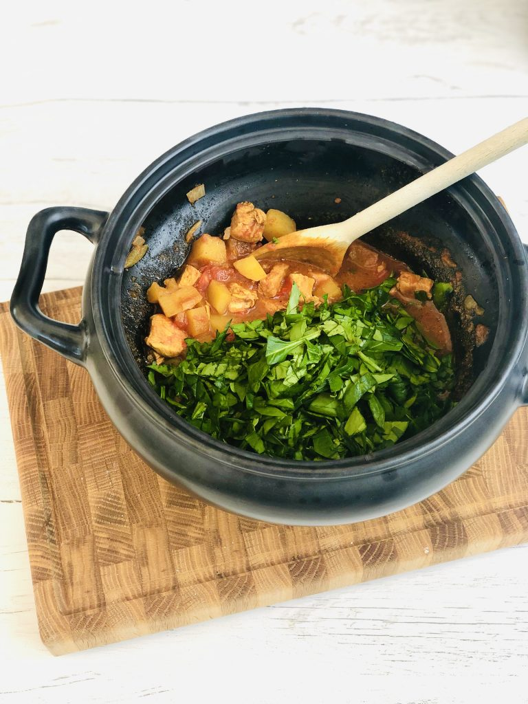 black slow cooker crockpot pan filled with cooked chicken curry and a pile of fresh chopped spinach has been tipped into pan ready to be stirred in