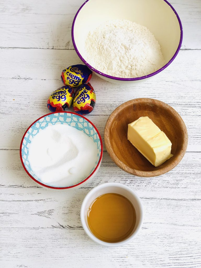 ingredients for creme egg cookies on a white table top - self raising flour in a white bowl with purple rim, three creme eggs, small blue, white and red bowl with sugar in, small wooden bowl with a block of butter in it and a small white bowl with maple syrup in it
