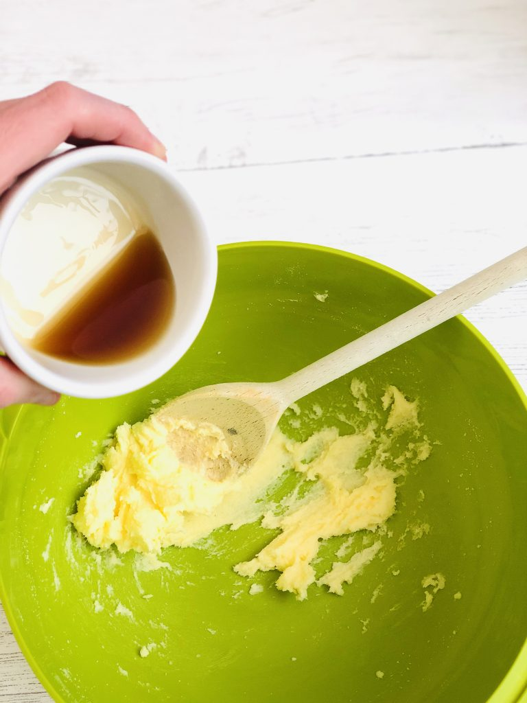 bright green joseph joseph mixing bowl with creamed together butter and sugar in the bottom with a wooden spoon reseting on the side - small white bowl of maple syrup being poured into the mixing bowl