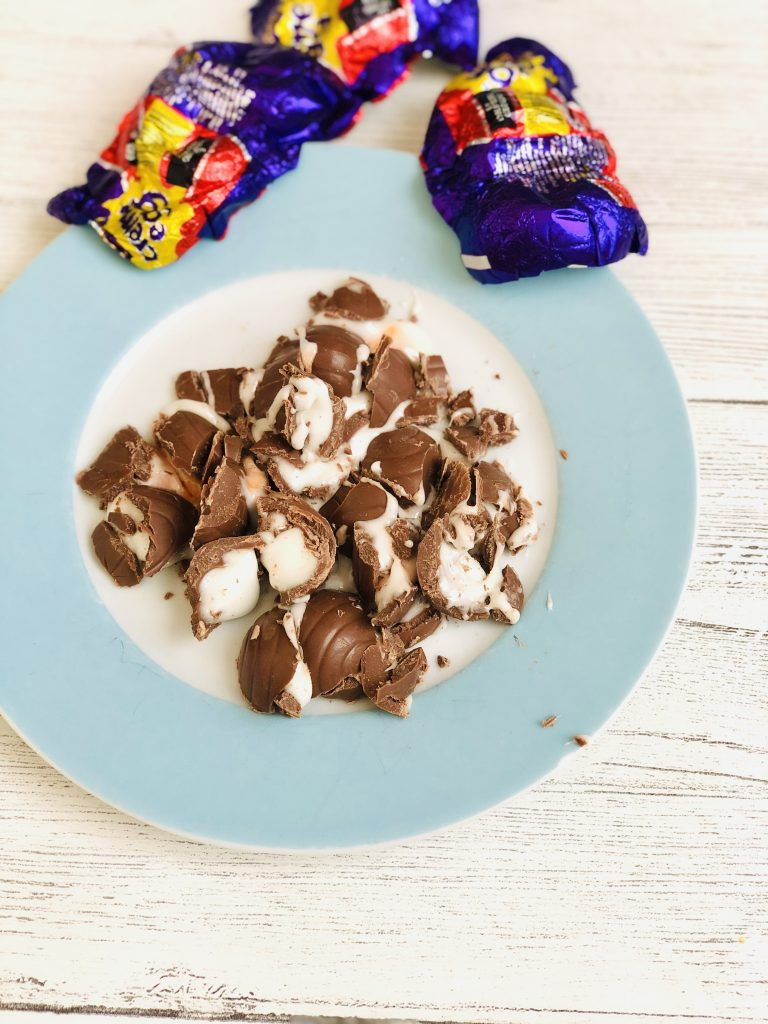 white plate with pale blue rim filled with chopped up creme eggs - three creme egg wrappers on the table next to the plate