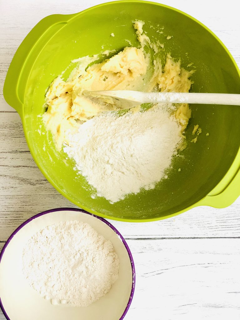 bright green joseph joseph mixing bowl with creamed together butte and sugar in the bottom with self raising flour just been tipped in ready to mix. Small bowl of self raising flour next to the mixing bowl ready to be added