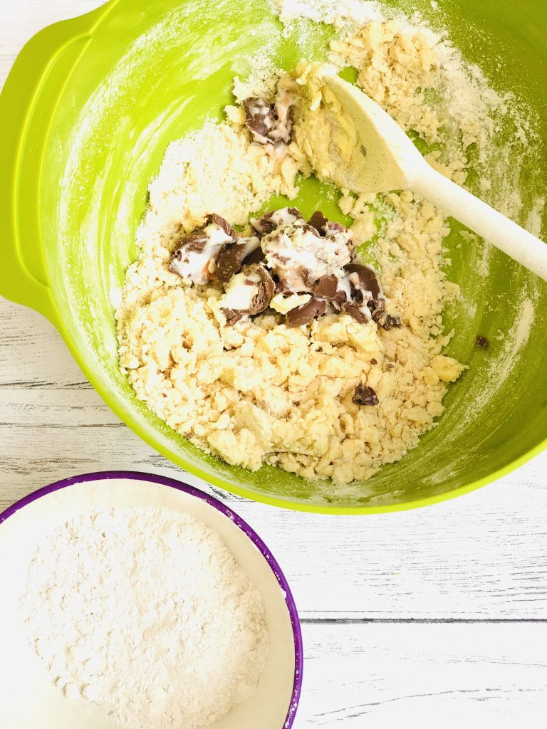 bright green Joseph Joseph mixing bowl with creme egg cookie dough mix being stirred with a wooden spoon - small bowl of self raising flour to the side of the mixing bowl waiting to be added