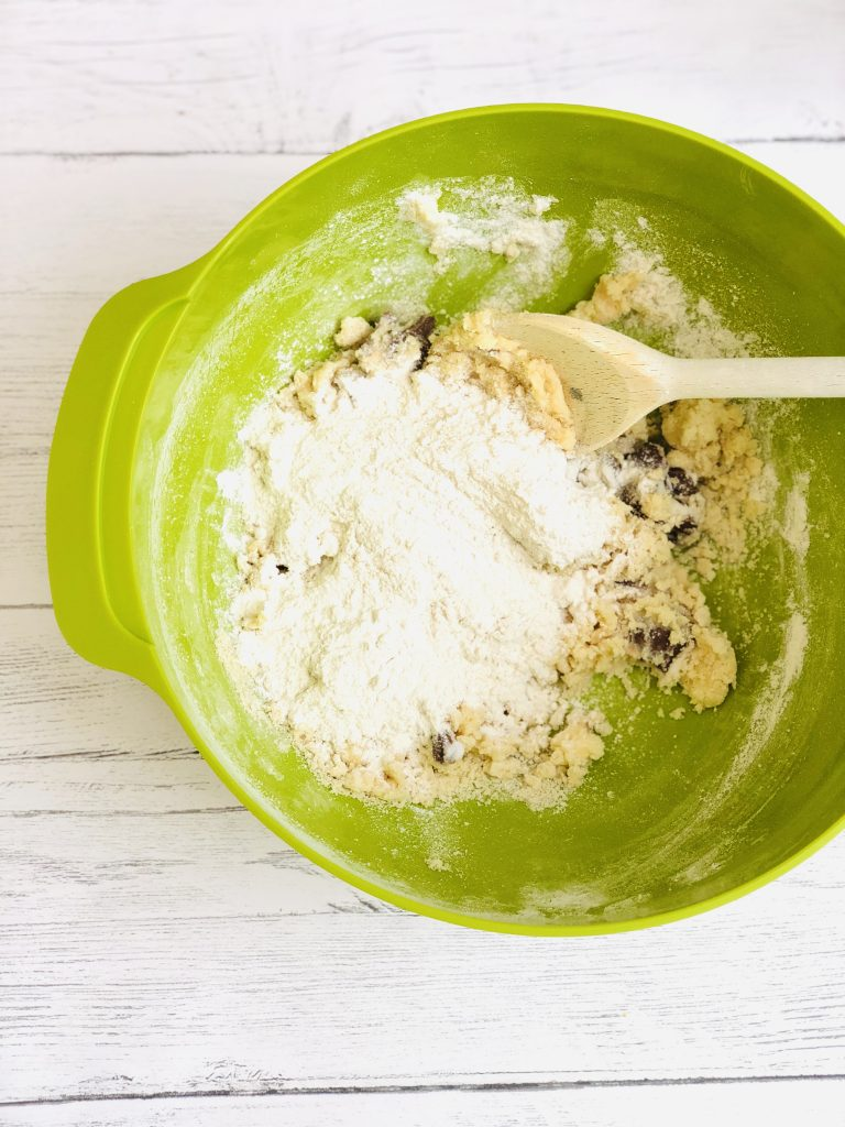 bright green Joseph Joseph mixing bowl filled with creme egg cookie dough being mixed with a wooden spoon
