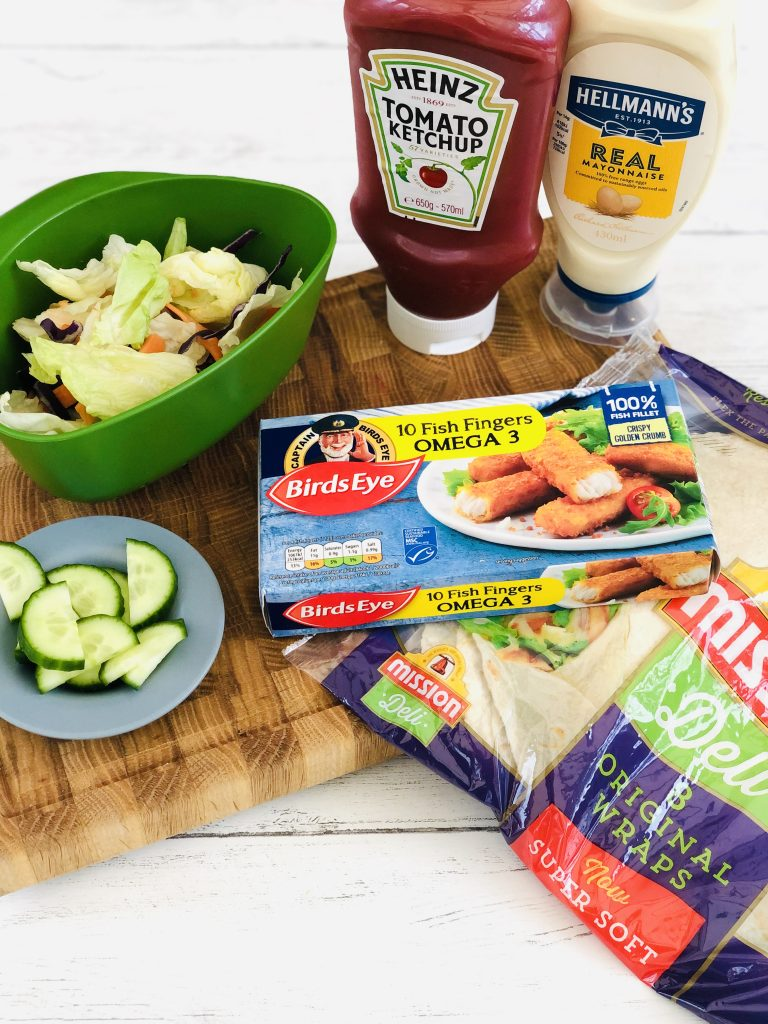 ingredients for fish finger wraps gathered on a table- box of fish fingers, pack of tortilla flour wraps, saucer of cucumber slices, joseph joseph mini colander filled with fresh salad leaves, bottle of Heinz tomato ketchup and bottle of Hellman's mayonnaise