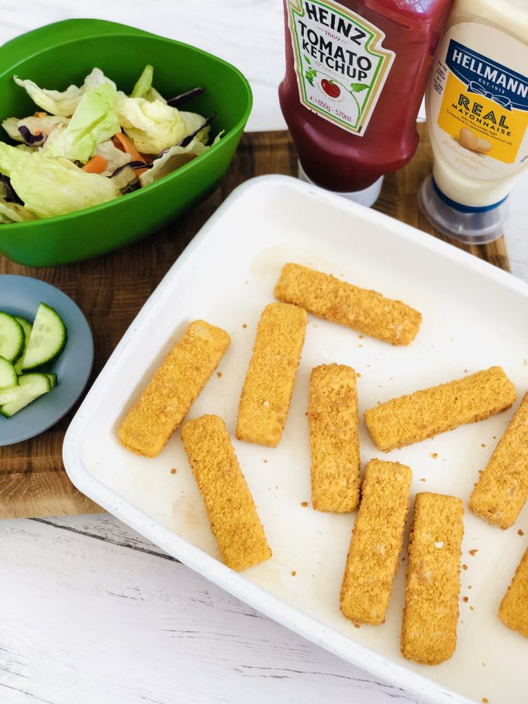 fish finger wrap ingredients - baking tray filled with fish fingers, cucumber slices on a plate, Joesph joesph green mini colander filled with fresh salad, bottle of heinz ketchup and hellmans mayonnaise in the background