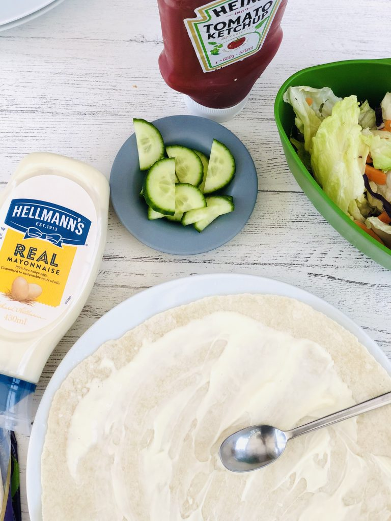 soft flour wrap spread with mayonnaise, bottle of tomato ketchup and mayonnaise next to the wrap along with cucumber slices and joseph joseph colander filled with fresh crunchy salad leaves