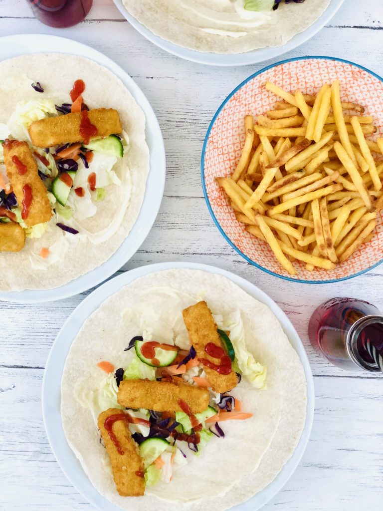 two plates with fish finger wraps on them - wraps have mayonnaise, salad, cucumber, fish fingers and a drizzle of ketchup - there's a bowl of chips and bottles of vimto with black and white striped straws