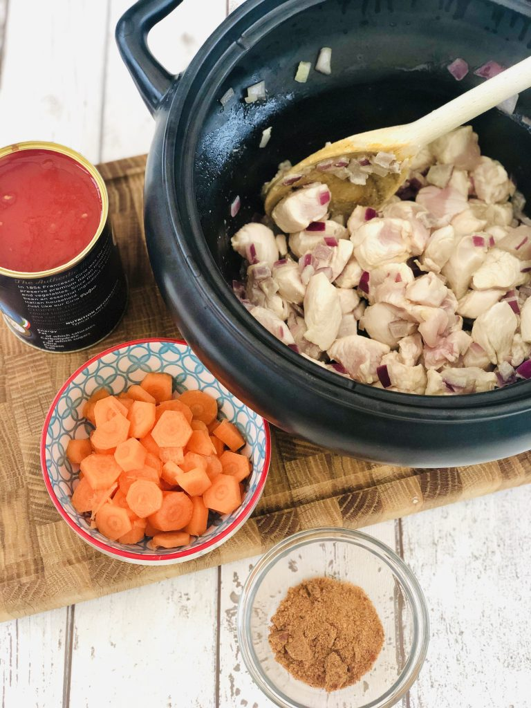 black crockpot slow cooker pan filled with sautéed red onions and diced chicken breast