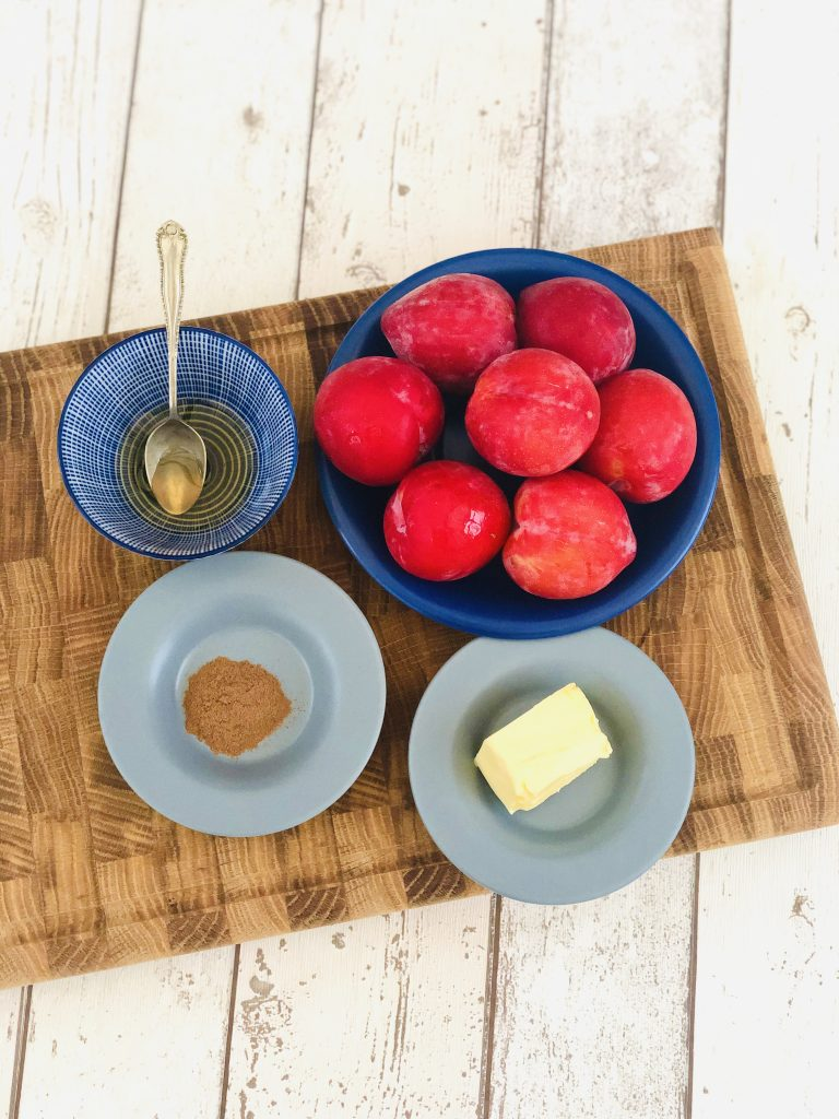 ingredients for plum compote gathered together on a wooden chopping board - blue bowl filled with ripe plums, small blue and white bowl with two tsp of honey, small blue saucer with a pinch of ground cinnamon and a small blue saucer with 15g butter