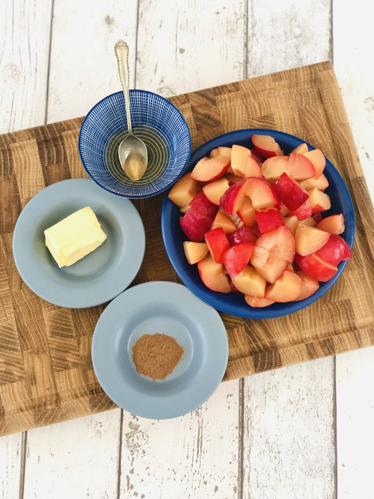 ingredients for plum compote gathered together - blue bowl filled with chopped plums, small blue and white bowl with tsp runny honey, small blue saucer with butter and a small blue saucer with a pinch of ground cinnamon