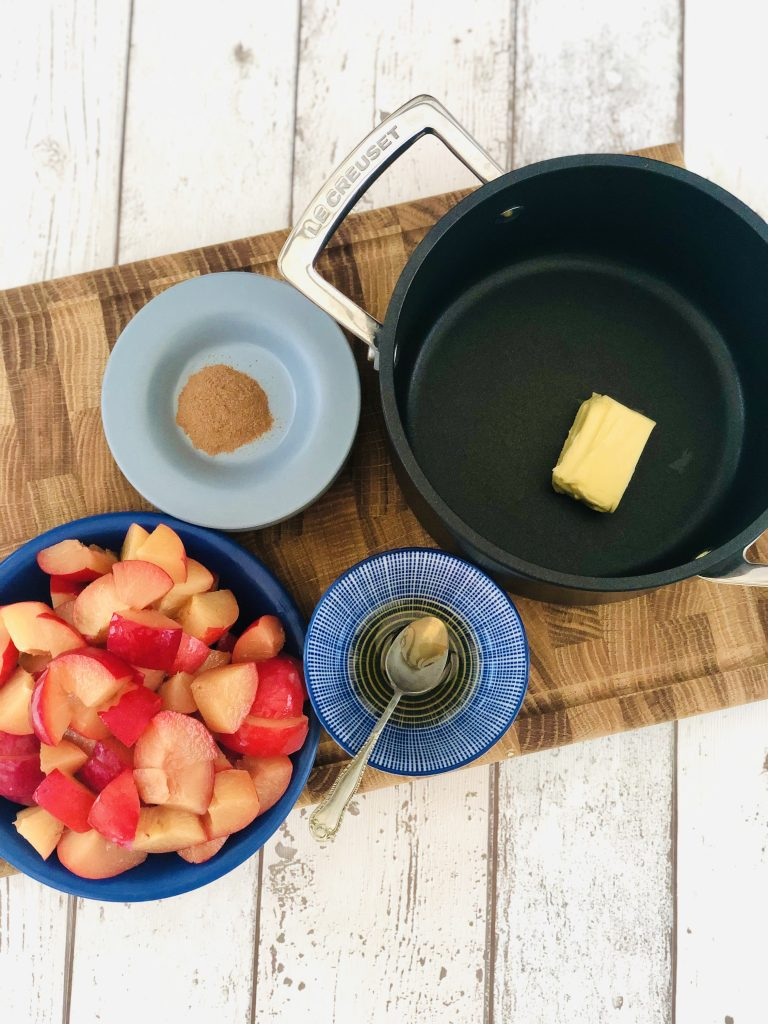 black le creuset saucepan with a knob of butter in it - wooden chopping board with chopped plums next to a small bowl of runny honey and small saucer with a pinch of ground cinnamon on it
