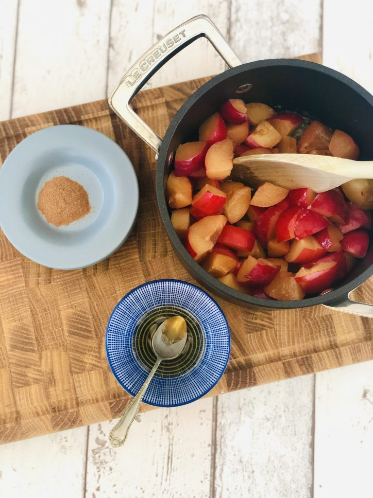 black le creuset saucepan filled with chopped plums, next to the pan is a bowl of runny honey and a pinch of ground cinnamon