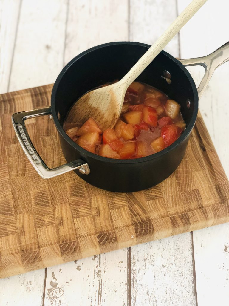 black le creuset saucepan with squashy cooked plum compote