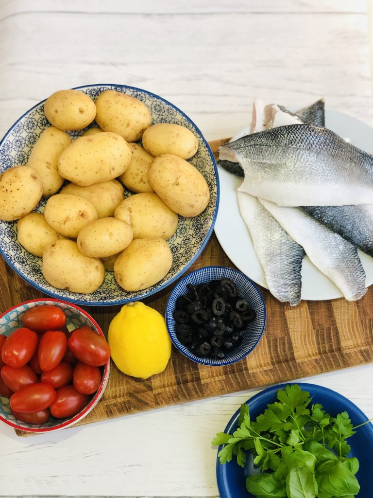 ingredients for sea bass tray bake gathered on a wooden chopping board - bowl of baby plum tomatoes, bowl of new baby potatoes, 4 sea bass fillets, bowl of black olives, lemon, blue saucer with flat leaf parsley and basil
