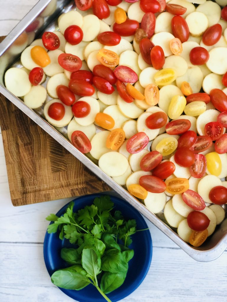 large roasting tin filled with sliced new potatoes and red, yellow and orange baby plum tomatoes - bunch of flat leaf parsley and basil on a blue saucer next to the roasting tin