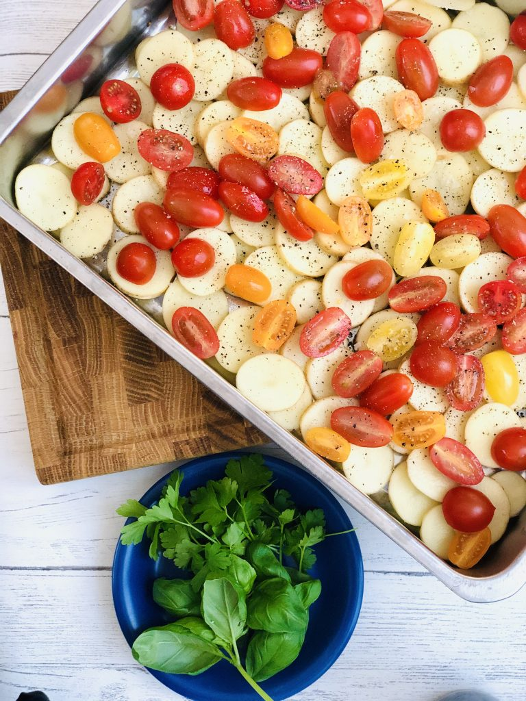 large roasting tin filled with sliced new potatoes and red, yellow and orange baby plum tomatoes scattered with sea salt and black pepper - bunch of flat leaf parsley and basil on a blue saucer next to the roasting tin