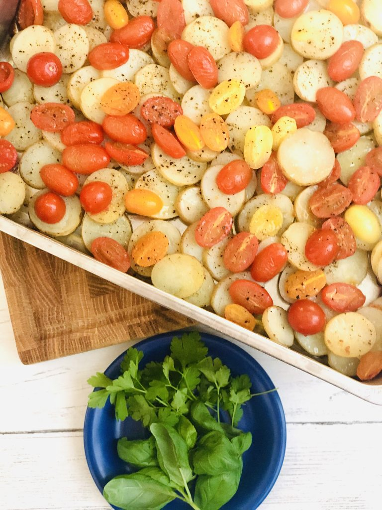 roasting tin filled with sliced new potatoes and halved plum tomatoes scattered with salt ad black pepper and drizzled in olive oil - baked in the oven for around 30 minutes until just turning tender - saucer of basil and flat leaf parsley next to the tin