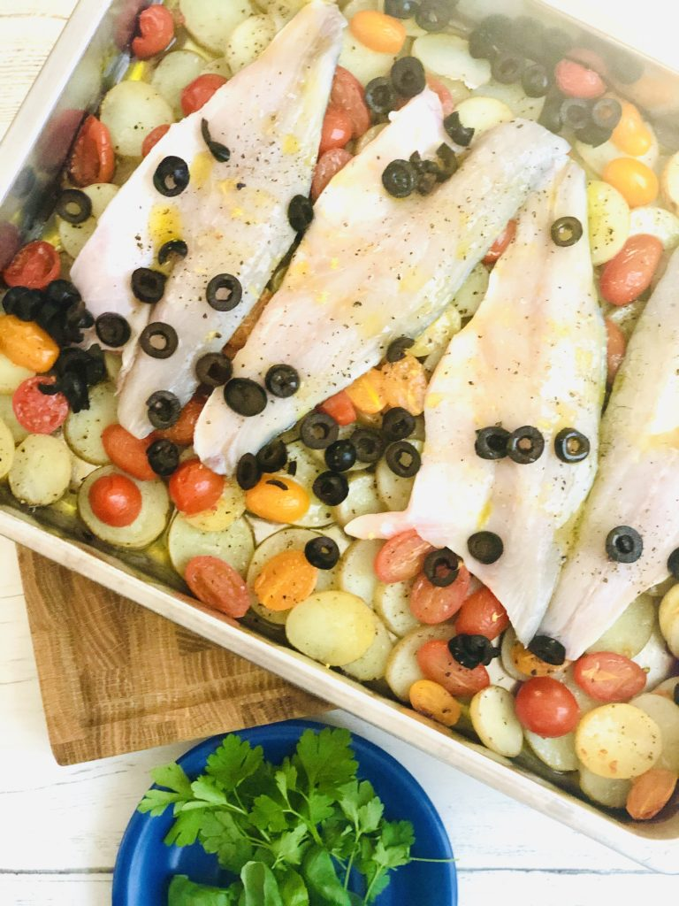 roasting tin with sea bass fillets laid on top of baked sliced new potatoes and baby plum tomatoes - sliced black olives scattered over the sea bass fillets