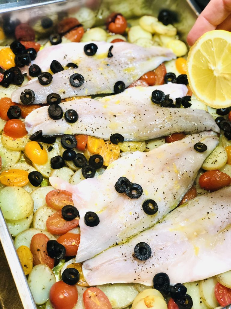 roasting tin with sea bass fillets laid on top of baked sliced new potatoes and baby plum tomatoes - sliced black olives scattered over the sea bass fillets - half a lemon being squeezed over the fish filets