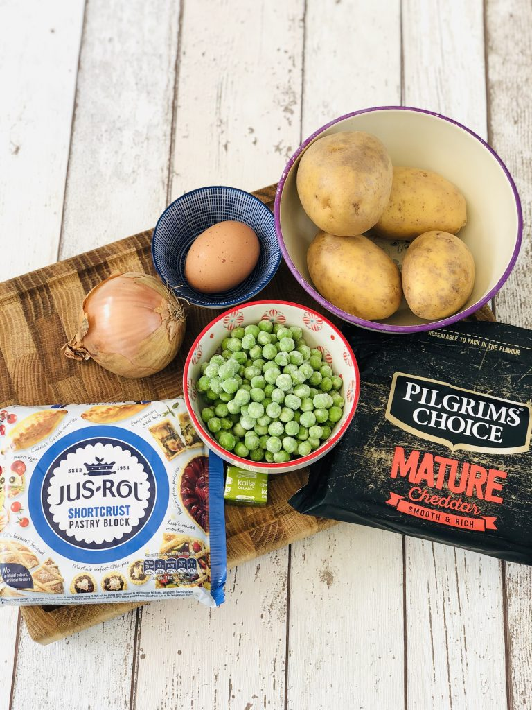 ingredients for vegetable pasties - jus rol shortcrust pastry, small bowl of frozen peas, vegetable stock cube, onion, egg, four potatoes, pack of mature cheddar cheese