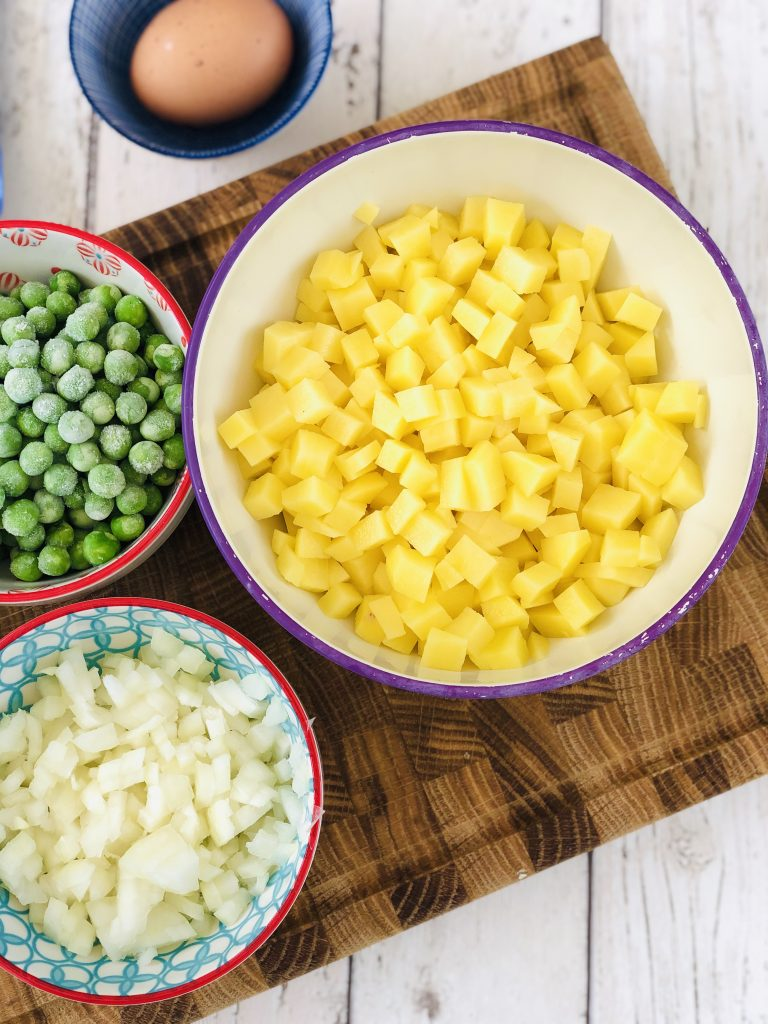 ingredients for vegetable pasties - diced potatoes, diced onions and frozen peas alongside an egg in a blue and white bowl