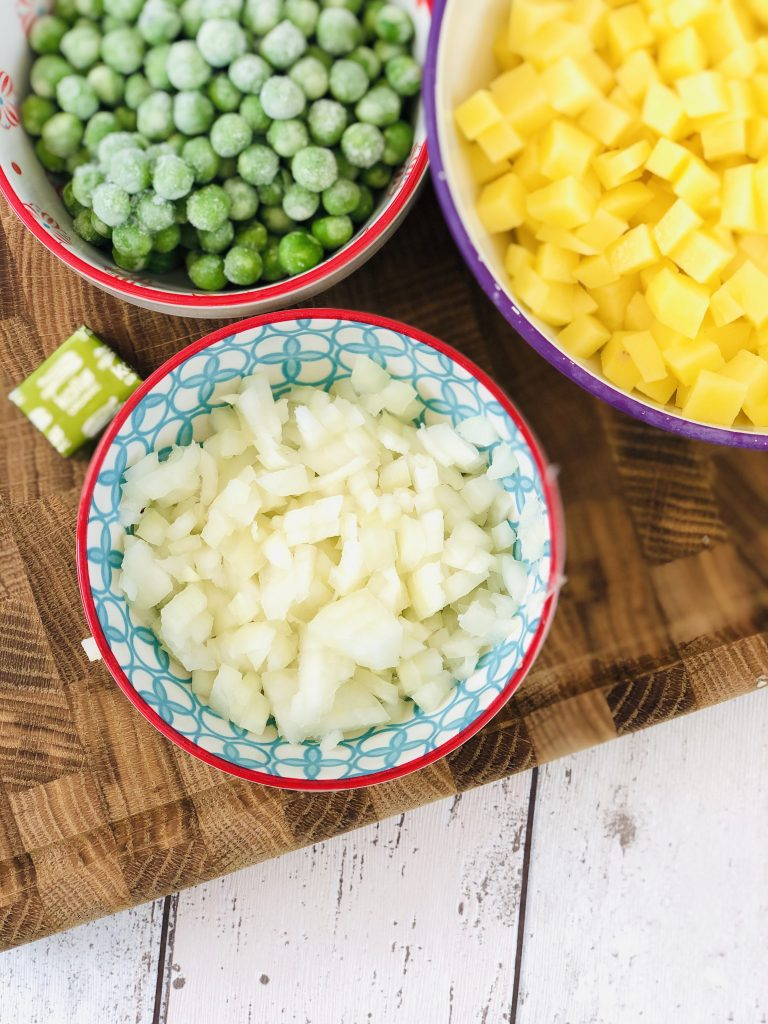 ingredients ready to make vegetable pasties - bowl of chopped onions, bowl of diced potatoes and bowl of frozen peas - vegetable stock cube alongside the bowls of vegetables