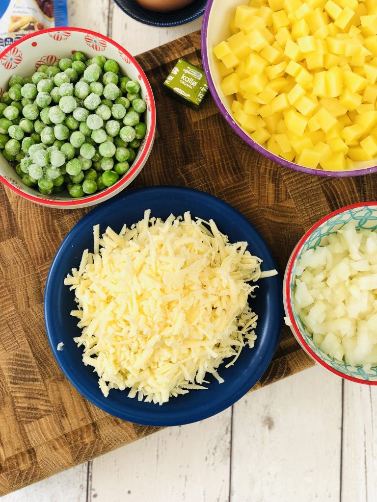 ingredients gathered ready to make vegetable pasties - bowl of diced potatoes, bowl of frozen peas, bowl of diced onions, plate of grated cheddar cheese