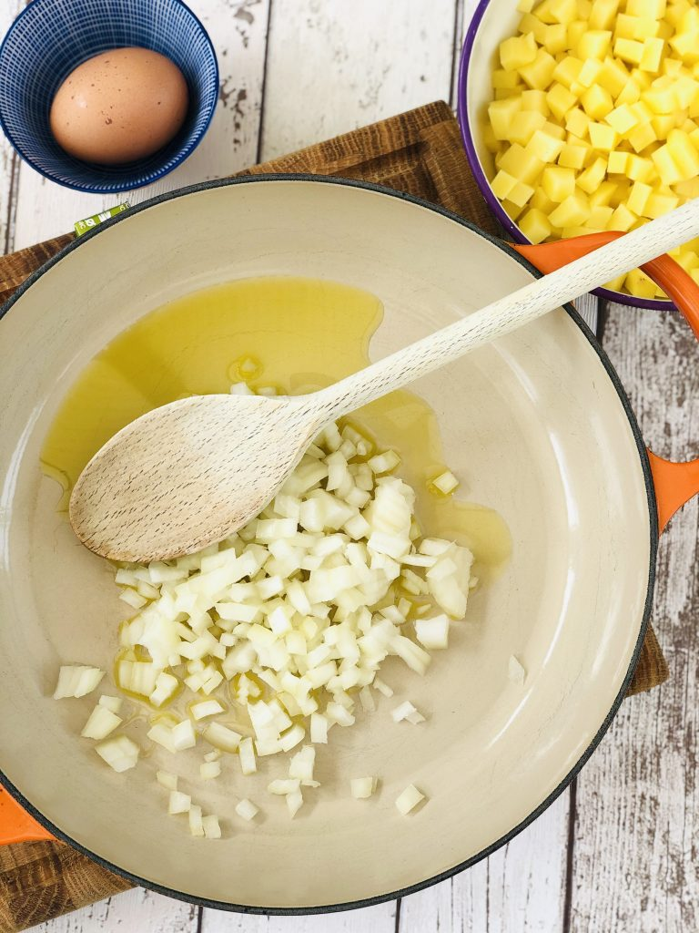 orange skillet pan with olive oil and diced onions in it - small bowl of diced potatoes to the side waiting to be added