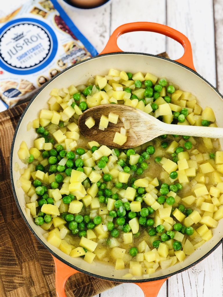 orange skillet pan filled with diced onion, potatoes and peas in vegetable stock - jus rol shortcrust pastry to the side of the pan