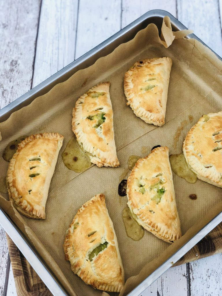 baking tray with six homemade rustic vegetable pasties fresh from the oven