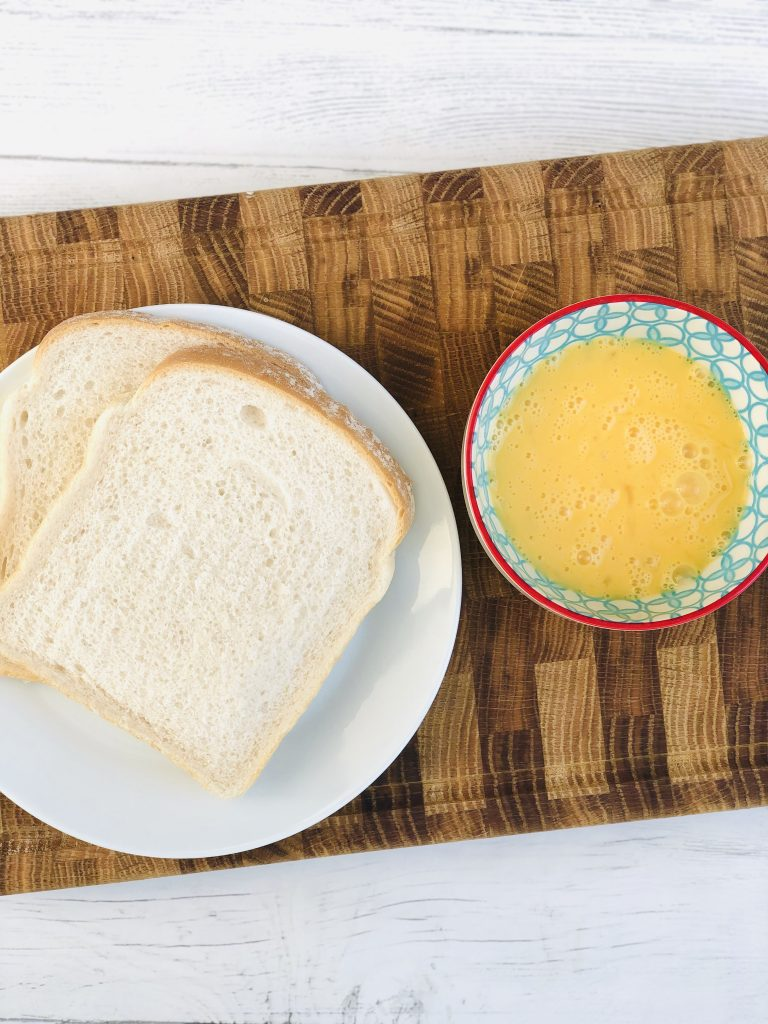 two slices of white bread next to red, blue and white bowl filled with beaten eggs
