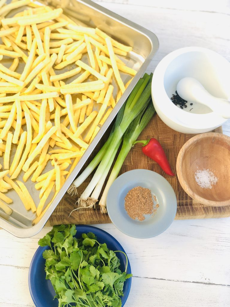 ingredients for homemade salt and pepper chips - tray of oven chips, 4 spring onions, szechuan peppercorns, red chilli, 5 spice powder, sea salt, bunch of coriander