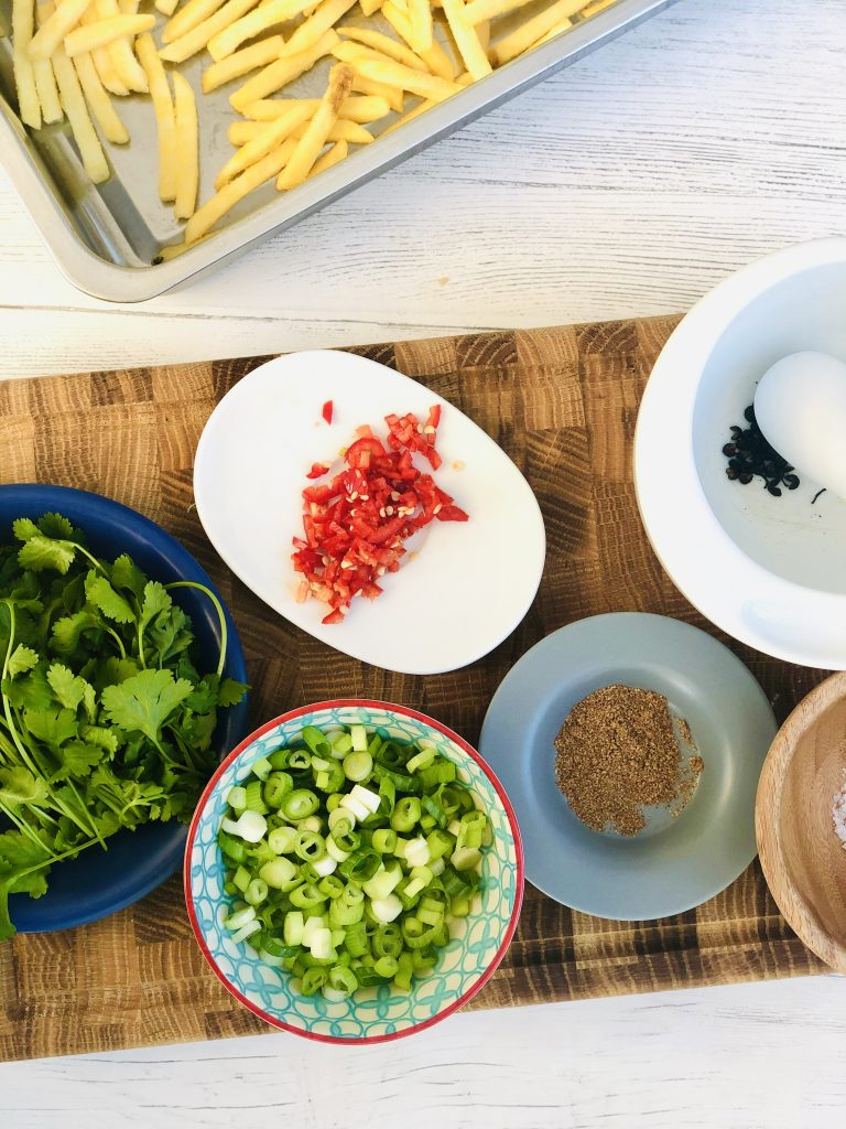 ingredients for homemade salt and pepper chips - baking tray filled with oven chips, bunch of coriander, bowl of sliced spring onions, finely chopped red chilli, saucer of 5 spice powder, Szechuan peppercorns in a pestle and mortar, sea salt flakes in a little wooden bowl