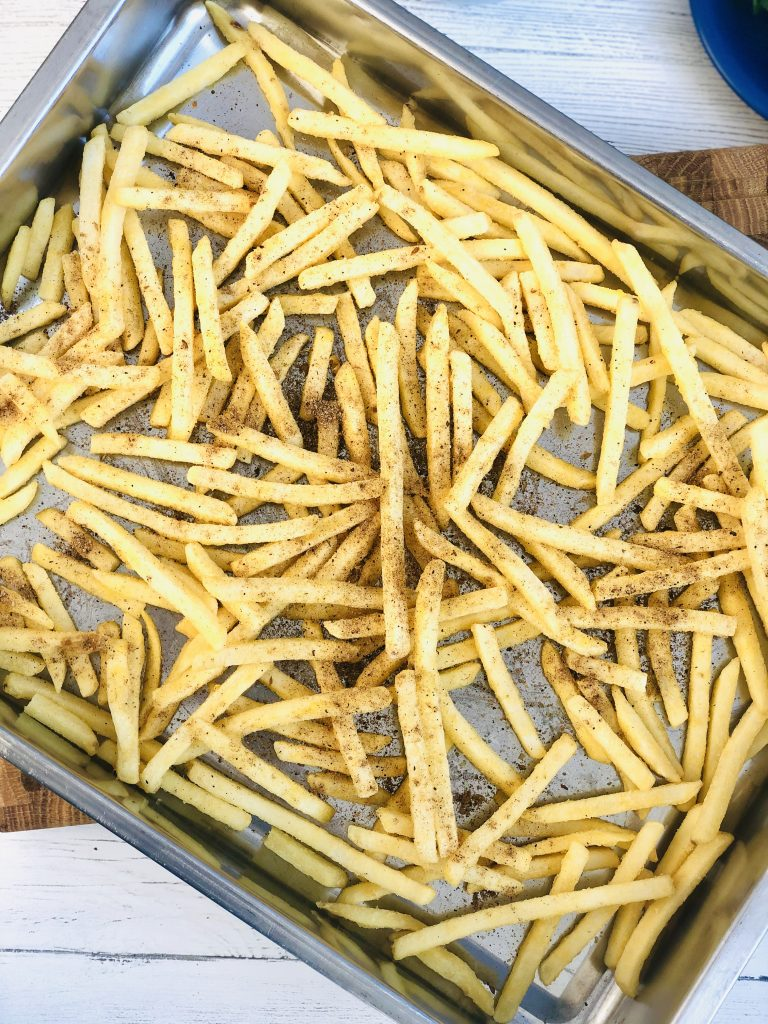 oven chips on a baking tray scattered with chinese spices ready to make salt and pepper chips