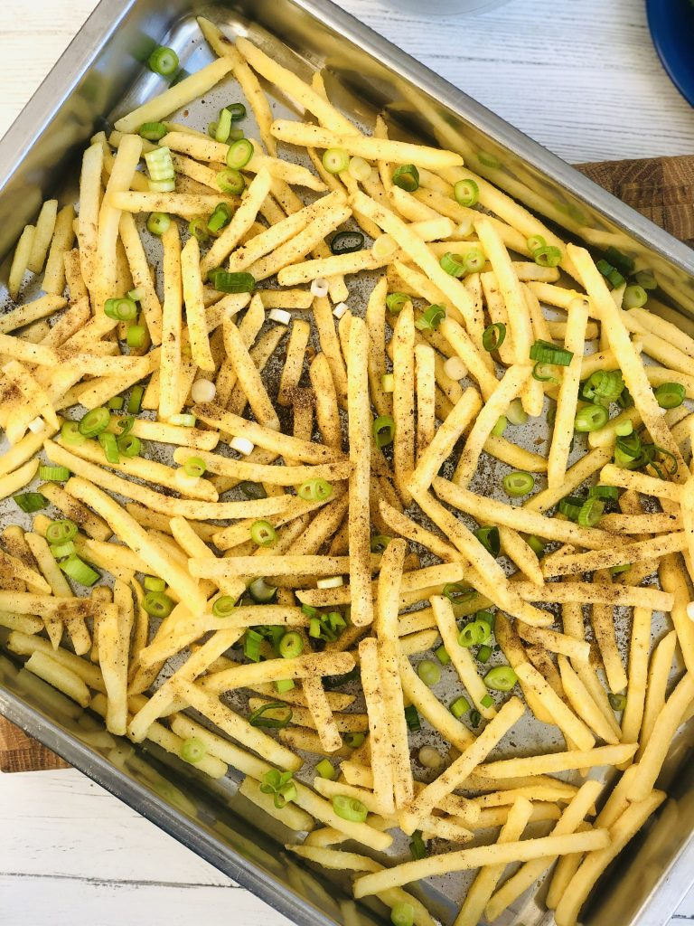roasting tin filled with oven chips scattered with sliced spring onions and chinese spices